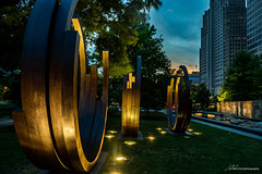 City Garden Rings (Jae at Wits End) Tags: park city blue trees sunset sky plant tree nature clouds evening twilight colorful dusk objects places publicart dim