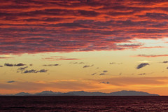 La Corsica dalla costa tirrenica in un tramonto infuocato (Paolo Romagnoli) Tags: light sunset sea cloud tramonto mare ray glow glare nuvola cloudy flash flare blaze sole rosso luce brilliance riflesso raggio bagliore