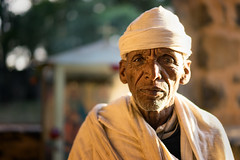The Gate Keeper (departing(YYZ)) Tags: africa travel portrait people man male church face hat zeiss robe sony christian 55mm fe ethiopia alpha orthodox a7 relgious goldenhour pilgrim gondar departingyyz sonnartfe55mmf18zalens