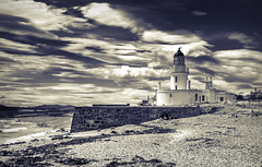 Channory Point Lighthouse (Uncle Berty) Tags: blue light sea sky bw lighthouse white house black beach monochrome yellow clouds point coast sand stones sandy pebbles coastal split toned isle bnw pebbly rosemarkie stoney chanonry toning fortrose