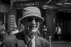 Sun Block (Leanne Boulton) Tags: life street old city uk light shadow summer portrait people urban blackandwhite bw sunlight white man black detail male texture monochrome smile face hat sunshine sunglasses closeup canon 50mm mono scotland living blackwhite eyes eyecontact natural humanity outdoor expression glasgow candid character culture streetphotography streetlife scene depthoffield human elderly age shade portraiture 7d grimace aged society tone facial tweed candidportrait candidstreetphotography candideyecontact