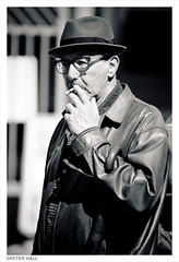 Smoker (peterphotographic) Tags: street uk portrait england blackandwhite bw man london monochrome hat glasses nikon britain cigarette candid smoke streetphotography sigma southbank smoker spectacles sigma70210f28 dsc7286 d300s camerabag2
