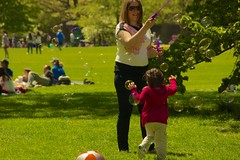 Bubbles on the Great Lawn (Ed Yourdon) Tags: park newyork grass sunglasses spring child centralpark manhattan lawn mother bubbles greatlawn