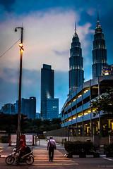 An Evening in Kuala Lumpur (Hadi Zaher) Tags: street city light architecture skyscraper dark lights evening crossing dusk centre famous petronas towers twin pedestrian icon motorbike malaysia kuala kl klcc lumpur