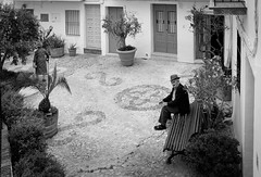 Spanish garden (streetstory) Tags: hat garden bench spain mosaic streetphotography oldman courtyard andalusia manandwoman fujix100t