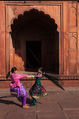 Whirling, Delhi (Marji Lang Photography) Tags: street travel girls red two people india playing colors wheel kids composition turn children fun happy photography daylight amazing colorful play wind couleurs delhi muslim islam spin streetphotography documentary happiness mosque twirl spinning mosquee swirl playful masjid swirling whirling streetshot chandnichowk jama jamamasjid whirl olddelhi happygirls travelphotography turningaround bigmosque muslimarea delhimosque karibaoli marjilang
