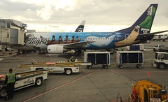 """Boeing Alaska Airlines jet parked the airport, painted motto """"We're All Pulling Together"""", sled dog, boat, beluga whale, a musher wearing a parka, International airport workers, Anchorage, Alaska, USA (Wonderlane) Tags: dog alaska clouds plane airplane boat airport workers all painted jet motto international anchorage together whale were trucks boeing beluga airlines musher sled 1928 c2 pulling carts parka sleddogmusher"""