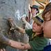 Jai, Maël et Marie-Soleil appliquent une couche collante de sable mélangée avec du tapioca afin de revêtir la terre argileuse dont est construite la maison. Province de Chiang Mai, Thaïlande.