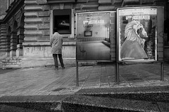 In front of a theater (PIXXELGAMES - Robert Krenker) Tags: vienna wien street white mystery dark poster theater looking streetlife rainy unknown fujifilm monochrom blacknwhite schwarzweiss fujinon biancoenero streetstyle volkstheater xt1 lifestreet manunknown