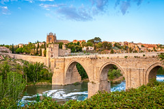 Panorama of famous Toledo bridge in Spain, Europe. (Konstantin Yolshin) Tags: old city travel bridge blue summer sky urban panorama cloud white house reflection building tree green tower castle tourism nature water beautiful stone architecture river landscape coast countryside town spain ancient scenery europe day arch peace view fort outdoor ripple pano famous horizon country landmark scene panoramic clear toledo province