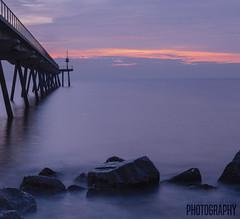 Desde abajo... (Judit Guijarro) Tags: ocean barcelona pink blue light sunset sea espaa orange water del puente mar agua nikon sunny reflejo pont catalunya seda roca mediterrneo petroleo efecto badalona ocano petroli d3100 nikond3100 sedaefect