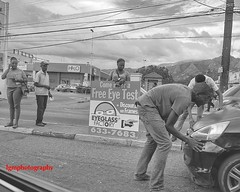 Free Eye Test (Halcon122) Tags: street bw sign downtown traffic accident candid streetphotography kingston ja olympusem5markii