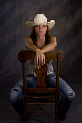 Cowgirl sitting (robocop1091) Tags: brown white hat female hair model chair cowboy long sitting tank bokeh top gray posing holes jeans cowgirl strobes lighing