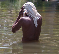 Man bathing in river (Sarah Burnage) Tags: india man hot water river asia fingers sunny towel cleaning bathe torso ripples bathing cloth waterdrops washing