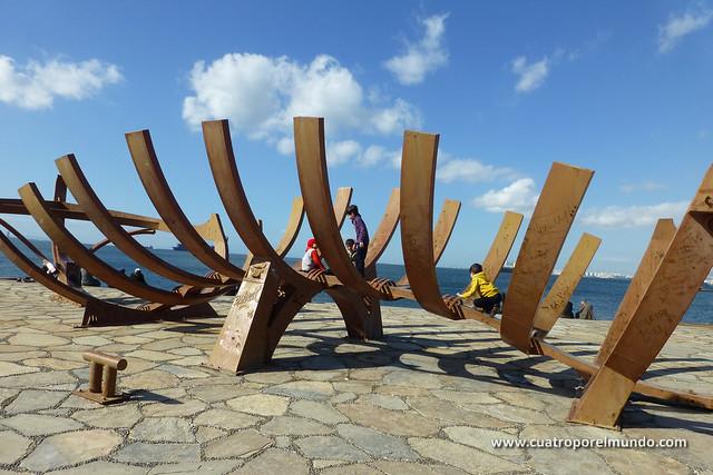 Jugando en una escultura en el paseo maritimo