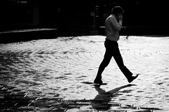 Walk and Talk (Leanne Boulton) Tags: life lighting street city uk light shadow portrait people urban blackandwhite bw sun sunlight white man motion black detail reflection male texture wet water monochrome mobile businessman shirt modern contrast canon reflections walking mono scotland living blackwhite high movement shiny phone glasgow circles candid telephone bricks working cellphone cell tie pedestrian scene communication business smartphone human shade area paving reflective conversation backlit posture gesture bandw talking rim tone concentric zone interaction vision:outdoor=0972