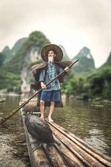 The famous fisherman (Syahrel Azha Hashim) Tags: china travel light vacation portrait mountain holiday mountains detail bird water colors hat birds clouds standing river cormorants beard fishing fisherman nikon colorful dof fishermen bokeh expression guilin getaway unique traditional details chinese paddle naturallight oldman scene bamboo tokina single portraiture elder handheld raft shallow moment simple dramaticsky paddling iconic conventional oneperson bambooraft traditionalclothing ultrawideangle colorimage workingtogether flightlessbird singleexposure d300s syahrel