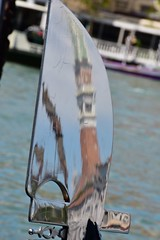St. Mark's Campanile Reflection on a Ferro (Crumblin Down) Tags: bridge venice red italy musician music food reflection clock water hat yellow shop mirror canal store italia mask pizza chrome ear gondola stick van gogh venezia gondolier selfie ferro forcola