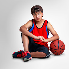 Teenager boy sitting with basketball on grey background with clipping path