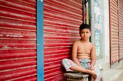 A Lazy Morning (Sheikh Shahriar Ahmed) Tags: street morning boy red store kid child streetlife dhaka bangladesh banasree dhakadivision sheikhshahriarahmed