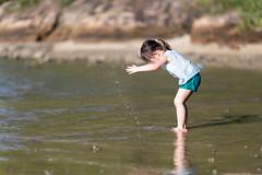 Spitting water. (hksleeper) Tags: girl bokeh dof hongkong asia canon 6d 135l beach water spit fun child green turquoise white rock sand