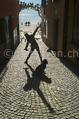 Happy (Mats Silvan) Tags: road street door shadow sea people woman dog pet sunlight lake playing color window water smile hat sunshine smiling animal stone happy person switzerland ascona ticino alley play streetlamp antique backlit positive raisedarms benchtree
