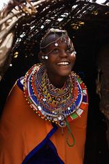 Maasai girl posing inside Inkajijik (Maasai hut) entrance, Kajiado area, South Kenya (Alex_Saurel) Tags: africa travel roof shadow vacation portrait people woman color cute girl beautiful beauty smile face smiling closeup architecture female necklace cabin pretty day cheek african femme traditional scenic culture photojournalism indoor headshot case bi