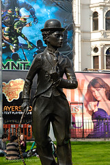 Statue of Charlie Chaplin seen against colourful posters in Leicester Square, London, England (Roberto Herrett) Tags: city uk travel england people urban cinema london english film tourism colors grass hat k vertical movie colorful comedy europe sitting colours unitedkingdom britain famous capital sightseeing cities places tourist billboard u comedian actor colored stick british colourful coloured sights locations stockphoto rherrettflk