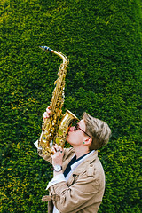 Young woman kissing the saxophone, green background (PrgomeljaDusanAna) Tags: light portrait people musician music woman white black girl beautiful beauty hat fashion lady female club standing hair studio person clothing concert model pretty artist play adult expression background performance young jazz blues style entertainment musical human talent sound instrument attractive elegant performer sax brass saxophone isolated elegance caucasian saxophonist