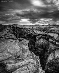 Fissure above Grjtagj Cave - HDR (Jonny Fay) Tags: road blue bw cliff white mountain black mountains ice nature water june clouds contrast landscape grey iceland nikon rocks mood moody view dynamic natural hill gray scenic dramatic ring crack solstice edge vista fjord cave grayscale hillside drama fissure greyscale d800 2014 cliffside grjotagja