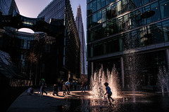 Around The Fountain (Places, Faces) Tags: london light lowkey shadows silhouettes action water jets waterjets central centre scene city robmchale street streetphotography streetscene streetphoto streets urban uk urbanstreets britain england playing kids family dayout sunny citylife moments people peoplewatching photography portrait perspective colour candid composition capture contrast compo