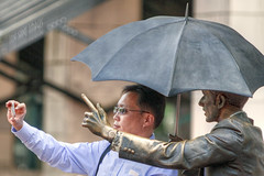 Psssst….Me Allow One Photo Under The Umbrella, Man! (Ian Sane) Tags: street camera two sculpture man oregon canon square portland lens ian photography eos is downtown phone mark candid broadway cell images ii 5d courthouse usm avenue morrison pioneer allowme 6th yamhill selfie sane umbrellaman ef70200mm f28l psssst…meallowonephotoundertheumbrellaman