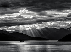 Howe Sound (martincarlisle) Tags: sky blackandwhite canada mountains water monochrome clouds islands britishcolumbia howesound sunbeams crepuscularrays highway99 seatoskyhighway niksoftware pentaxians tamronlenses pentaxart pentaxk5 silverefexii