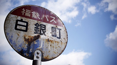 Waiting at the bus stop, Tsuruga-shi (Eric Flexyourhead) Tags: city blue sky urban white detail bus sign japan clouds japanese rust rusty busstop kanji worn  weathered characters puffy 169 fragment tsuruga 17mm zd fukuiken   tsurugashi olympusem5 olympusmzuikodigital17mmf18