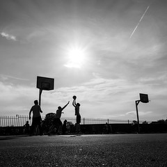 players (jaumescar) Tags: light shadow sky bw sun white black game monochrome field silhouette basketball sport clouds contrast work canon ball square team movement play basket space empty dramatic player negative teamwork lightroom