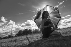 Holding the umbrella (rossellanot) Tags: park sky bw woman sunlight nature grass sunshine silhouette dreadlocks clouds contrast umbrella blackwhite arty sunny blackdress blackwoman