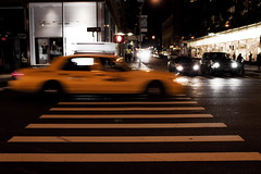 The City That Never Sleeps (jezselten) Tags: life street city urban usa ny newyork black blur never building car yellow night america dark walking moving waiting sleep cab taxi blurred stop crosswalk sleeps stopped strret shope