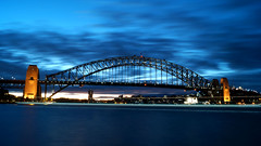 Sunset at Harbour Brigde, Sydney (gabrielafundora) Tags: ocean city longexposure travel bridge blue light sunset sea sky water colors night clouds contrast dark lights bay harbor mar harbour sony sydney windy australia landmark arquitecture lighttrail