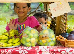 In Taha,a - Society Islands, Polynesie Francaise (Timothy Hastings) Tags: blue sky water smile fruit kids children french island polynesia stand nikon child smiles wave tropical nikkor sell talaa d810 fruitstan