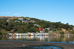 Colours of the Rainbow (Jocey K) Tags: houses sea newzealand sky colour water architecture clouds reflections rocks day stones clear southisland raod bankspeninsula boatsheds duvauchelle