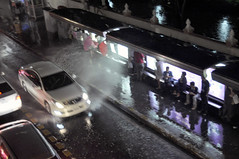A spray and away (Roving I) Tags: streets rain weather thailand evening bangkok vehicles publictransport umbrellas sprays splashes