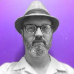 Selfie in Thrift Store Dressing Room (swampzoid) Tags: man hat beard glasses purple onecolor gayman