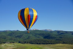 Balloon Over Angel Fire (Roger Blakey) Tags: blue sky mountains hot angel landscape fire air balloon multicolored balloonfest