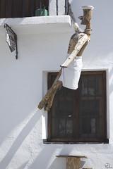 Entre el cielo y el suelo. (elojeador) Tags: ventana reja madera escultura fachada cartel colgado capileira cocinero soga regadera lasalpujarras pizzera baranda elojeador contendenciaaquedarmecalvo