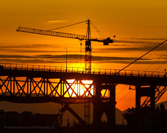 After being up in the sky all day, the sun gets very tired.  A Morrow crane helps lower her softly as the day ends. (Brendinni) Tags: seattle bridge sunset urban orange sun mountains silhouette clouds landscape construction glow crane illumination burnt sunsetglow seattlewa constructioncrane morrowequipment liebherrconstruction