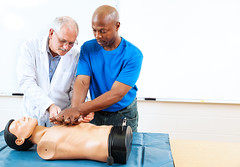 Doctor teaching first aid CPR techniques to an adult, African-american student.  Room for text. (olaruwaju) Tags: adult adulteducation african africanamerican black cardiopulmonaryresuscitation caucasian chestcompression class classroom cpr desk diversity doctor doll dummy education emergency emt ethnicity firstaid healthcare instructor learning lifesaving male man mannequin mature medical minority people person physician practice procedure school student table teacher teaching training