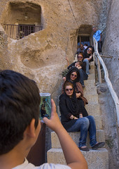 Tourists Taking Pictures In Front Of A Carved Home In The Village Of Kandovan, Iran (Eric Lafforgue) Tags: agingprocess architecture asia buildingexterior builtstructure carving chandovan city colorimage colour cultures day design environment eroded groupofpeople history house humansettlement iran iran0295 islamicrepublicofiran kurdish middleeast mobilephone mountain nonurbanscene outdoors people photography residentialstructure rock rockformation roof sculpture sitting sky stair togetherness tourism tourist town travel traveldestinations troglodyte valley vertical village weathered westernasia kandovan vision:people=099 vision:face=099 frs  ir iraan   belarusian ukrainian iran    iro   pers persia persien