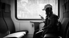 On the train - Helsinki, Finland - Black and white street photography (Giuseppe Milo (www.pixael.com)) Tags: street city urban blackandwhite bw white black girl monochrome contrast train finland photography photo helsinki europe fuji phone candid streetphotography faceless fujifilm seating onsale 27mm fujix xt10 fujixt10