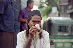 Tea at 1300 Hours (Sheikh Shahriar Ahmed) Tags: street man film analog beard 50mm tea drink candid streetlife fujifilm dhaka f18 bangladesh candidportrait nikonf6 rampura tupi af50mmf18d fujicolorc200 dhakadivision epsonv330 rampurabazar sheikhshahriarahmed