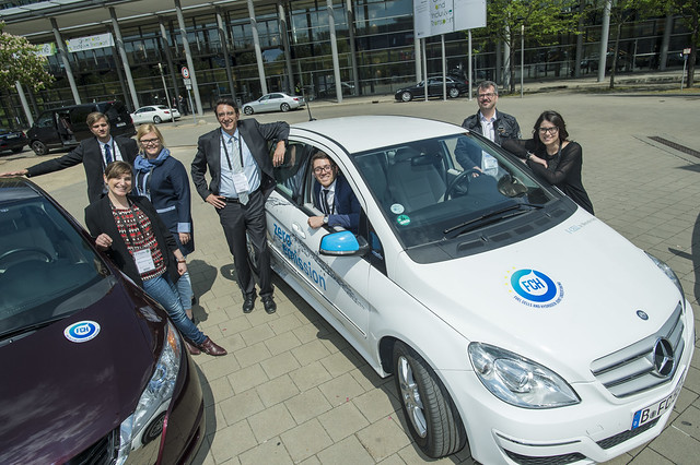 Attendees pose next to a fuel cell powered car